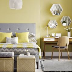 Contrast a soft yellow backdrop with cool grey upholstery and pale wooden furniture for a contemporary look.