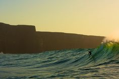 Irish surfer Fergal Smith dropping in at Aileens along the Cliffs of Moher.