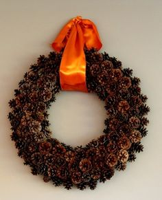 Holiday Crafts: Pinecone Wreath just change the ribbon from orange to red and your ready for Christmas! And maybe add some glitter!