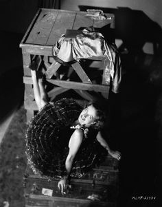 American actress Joan Crawford perches on a large trunk wearing a ballerina's costume 1928