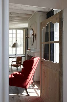 The white washed wood door & bright chair