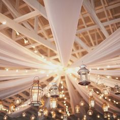 A mix and match of floating lanterns and candles among thick strands of tulle makes for one bewitching ceiling.