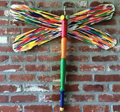 Flying with Rainbows and Unicorns - dragonfly creation from Winging This. This recycled and repurposed lawn art is made of ceiling fan blades and table leg adorned with a wine bottle stopper.