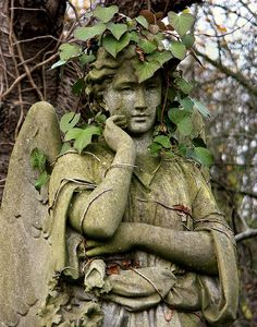 Highgate Cemetery, London, England..-This angel has stood guard for so long she now has a vine crown of greenery that suits her very well. Devine!