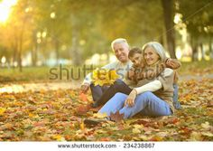 Grandparents and grandson together in autumn park - stock photo
