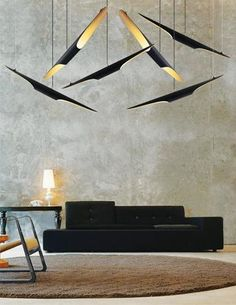 Coltrane by Delightfull features powerdercoated gold on the inside, dark matte on the outside and stylized iron tubes suspended overhead which resemble birds in flight. www.delightfull.eu
