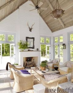 Dreamy summer cabin living room with sky-high vaulted ceilings, wicker furniture and pops of purple.