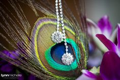 Wedding day silver drop necklace on a peacock feather and orchids.