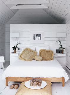 "Beachy Bedroom    A sea of white creates the perfect casual retreat.      In the boathouse's narrow upper-level bedroom, Michelle installed floating ledges flanking the bed. ""Having no tables or table lamps lends ease to a tight space,"" she explains. The antique French sconces, which the couple had owned for years, were painted white and capped with elongated contemporary shades."