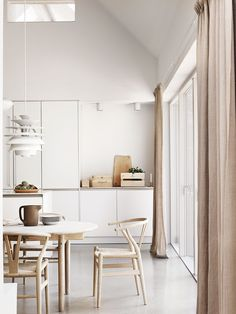 Simple and harmonious Scandinavian kitchen with dining table. Neutral colours…