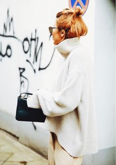 An oversized white turtleneck sweater is worn with camel pants and a small black bag.