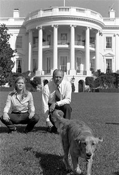 President Gerald Ford and his daughter, Susan, sit on the White House lawn and watch their golden retriever, Liberty, play on October 6, 1974.