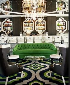 Fantasy entertaining room, with a tufted green couch in front of a stunning glass bar setup