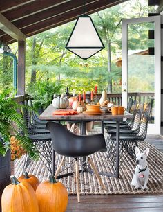 Get festive this fall by adding orange hues, pumpkins and gourds to your porch. Why not take dining outdoors and enjoy the cooler, crisper weather? Pictured here is a Glacier light from the Brian Patrick Flynn collection for Crystorama. #FallPorchDecor #FallPorchIdeas #FallDecorIdeas #FallHomeDecor