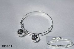 """Solid sterling silver Hawaiian Keiki (Baby/Child) adjustable Bangle. Features hand carved Hawaiian Princess Scrolls and a Plumeria (frangipani) flower. The band width tapers from 5mm down to 1.50mm (at the adjustable section). High Polish Finish, adjusts to fit. Two jingling bells attached. Features: The Word """"Makamae"""", in Hawaiian, means """"Precious"""", describes this stunning piece perfectly! This beautifully hand-crafted adjustable bangle is a precious keepsake"""
