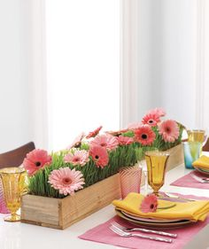 "A field of gerbera daisies and wheatgrass ""grow"" charmingly in a rustic table runner. 