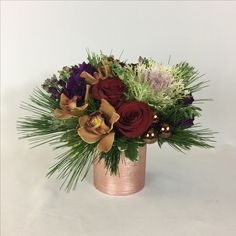 Red roses, hydrangea, Princess Pine, ornamental kale, cedar and piñon cones in this holiday floral arrangement.