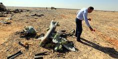 Un funcionario egipcio deja flores junto a restos del avión ruso caído en el desierto del Sinaí, tragedia de la que no se saben las causas.
