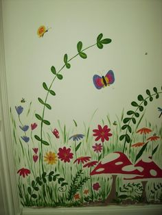 This is the early stages of the Rainbow Garden Mural, the mural covered two walls. One wall featured the rainbow and fields the other wall featured many plants, flowers, butterflies and bunnies.