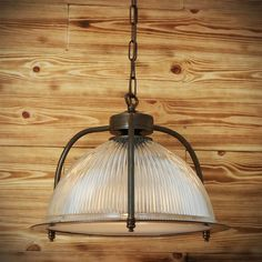 Manufactured in Ireland, this quality solid brass and prismatic holophane glass pendant is reminiscent of traditional industrial Pendant Lights with a protective brass cage.
