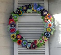 wreath of crochet flowers! Great idea~ I would mix it up with different flowers and maybe add a butterfly or little bee. So pretty and colorful!