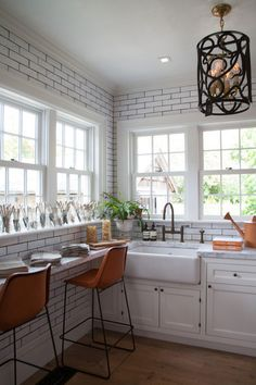 The slim breakfast bar under the windows make this country kitchen feel much larger and makes it more functional, while the graphic subway tile walls have a unifying effect.