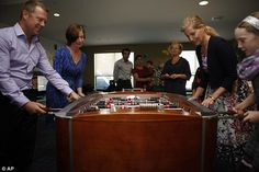 Fun and games: Sophie, Countess of Wessex, right, plays table football with Abigail McCorquodale, 10, a former patient, and her parents Doug and Brenda at Jeneece Place, a children's health foundation in Victoria