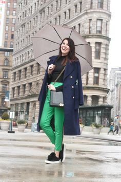 Bright green trousers with navy blue trench coat | umbrella rain street fashion photo, spring trends | Greta Hollar