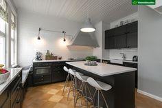 1900-luvun alussa rakennetun huvilan remontoidussa keittiössä vallitsee ihana tunnelma. Keittiön mustat kaapistot, valkoiset tiililadotut seinälaatat sekä kaunis parketti muodostavat hurmaavan kokonaisuuden, johon vanha nurkassa sijaitseva puuhella tuo tuulahduksen entisajoista. Jielde Signal-seinävalaisimet tuovat keittiöön kauniin valaistuksen.