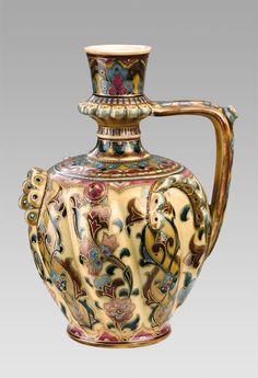 Zsolnay porcelánfajansz, kerek talpon álló öblös füles forma színesen festett virágmintás és rátétes díszítéssel.  Jelzett: máz alatt kékkel, ZSOLNAY PÉCS TJM öttorony és benyomott ZSOLNAY PÉCS.  1800-as évek vége. Magasság: 29 cm