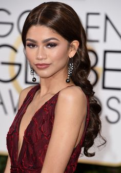 Zendaya stunned the world with her sleek center part, purple smoky eyes, and bold pout at the Golden Globe Awards