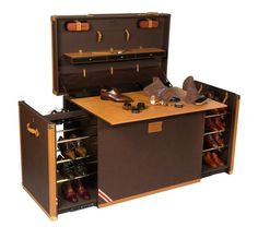 Shoe storage and maintenance trunk. With the shoes stowed and the sides pushed in, the fold out wooden work surface can be used simply as a classic portable desk