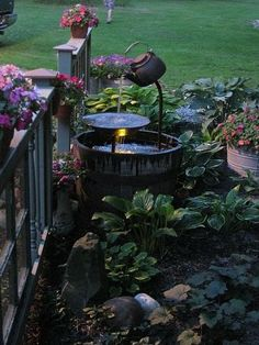 DIY Yard Fountain using whiskey barrel, old teapot, flat plate, and some tubing {hometalk - a website filled with inspiring garden photos}