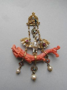 late 16C Pendant; gold; enamelled and jewelled; shaped, pierced plaque; Virgin(?) with chalice; quatrefoil pendant at base between two chains attached to pelican in her piety with jewelled wings and baroque pearl for breast; below: monster in coral attached by loops from which hang three quatrefoils with pearl at base of each.