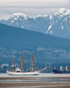 The New World . Tide out at the Spanish Banks as a tall ship heads east into English Bay. That's the ARC Gloria from Colombia visiting Vancouver. Looking across the bay at West Vancouver North Vancouver Lions Gate Bridge and beyond to snowcapped Mt. Elsay and Mt. Seymour Provincial Park. Captured in Vancouver British Columbia Canada May 2 2017