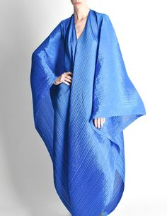 """Jaw dropping vintage Pleats Please piece by Issey Miyake. The possibilities are endless with this piece. An electric cobalt blue micro pleated fashion, that is multi-functional - a cape, wrap, dress, and poncho. Large, draping rectangular panel, with a dual V neck hole, open sides, and train at back. Issey Miyake's Pleats Please designs are revolutionary - """"The fabric's 'memory' holds the pleats and when the garments are liberated from their paper cocoon, they are ready-to wear"""". This…"""