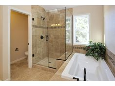 Bathroom With Large Tub And Stand Up Glass Door Shower Natural Light Brightens Up This