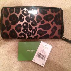 HP Kate Spade Lindenwood Animal Print Wallet 100% Authentic  Used only once for a nice dinner- this wallet is GORGEOUS  Black and brown print with leather trim. 14 karat gold plated hardware, logo panel on front. 12 credit card slots. 2 bill folds. Exterior slide pocket. Signature pattern inner lining. Original tags included (located in middle coin compartment). kate spade Bags Wallets