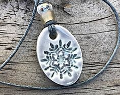 Tiny denim blue polymer clay oval pendant with stamped snowflake