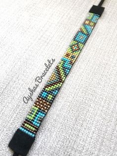 Handmade Bead Bracelet with Japanese Miyuki Delica Beads (bead loom) 7 different colours were used in this bracelet. This bracelet is 14 cm length and because of its suede ending it is adjustable and would fit wrists between 14 cm - 28cm . If your wrist size is different please