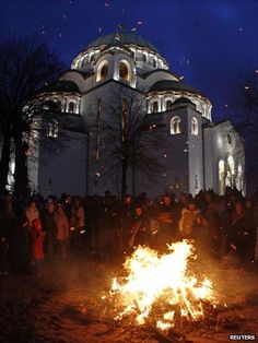 People burn dried oak branches, which symbolise the Yule Log, on Orthodox Christmas Eve in front of the Church of St Sava in Belgrade, 6 January