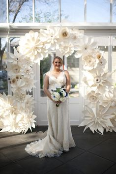 Arch covered in paper flowers - move to reception as backdrop for bride & groom's table