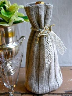You can repurpose an old sweater to make the perfect holiday gift. Felt the sweater (by washing it in hot water and drying it in a warm/hot dryer)  and sew the bottom to create a wine bag. Complete the look with metallic ribbon and a sparkly pin.