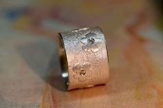 Breiter, silberner Ring mit aufgeschweißten Blüten, in welche jeweils ein naturfarbener Brillant eingefaßt wurde. Der Ring ist trotz seiner Breite von 14mm angenehm zu tragen, da die Ringstärke nur...