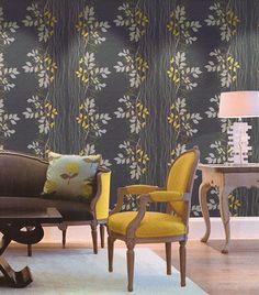 O papel de parede em tons de cinza é uma ótima opção para deixar a sala mais confortável e aconchegante, combinando bem com móveis coloridos.