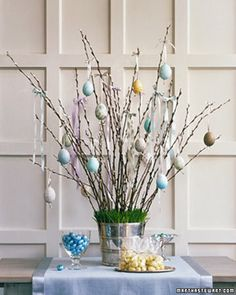 Hang decorative egg ornaments from pussy willow branches anchored in a bucket or vase with moss tucked in around the edges. (Courtesy Martha Stewart.com)