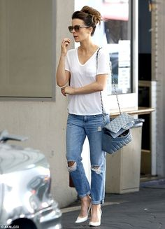 Kate Beckinsale is effortlessly stylish in a plain white t-shirt, cuffed torn denims and white pointy stilettos. She completed her look with a Chanel handbag and large sunglasses. The Underworld actress wore her hair in a large but loose bun. via dailymail.co.uk