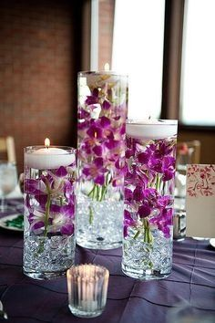 Purple orchids submerged in cylinder vases