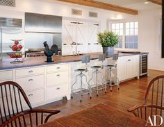 """In the kitchen, Blake created """"barnlike cabinet doors using strap hinges and rat-tail pulls,"""" she says. They are copies of ones she salvaged from a barn owned by the late actor George Montgomery. A circa 1890 cast-iron windmill weight is on the counter. The range and custom hood are from Wolf. Refrigerator, Sub-Zero."""