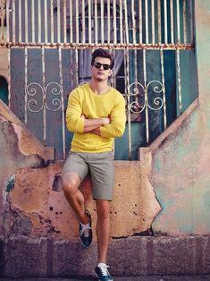 Shop this look on Lookastic:  http://lookastic.com/men/looks/yellow-crew-neck-sweater-grey-shorts-black-sunglasses-navy-low-top-sneakers/10430  — Yellow Crew-neck Sweater  — Grey Shorts  — Black Sunglasses  — Navy Leather Low Top Sneakers